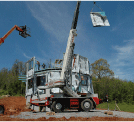 Image of a construction site with equipment hoisting a panel