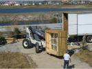Image of a construction site with a terex truck hositing windows
