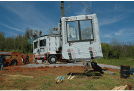 Image of a construction site with equipment hoisting a panel from another view
