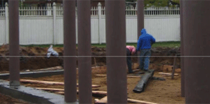 Image of several 20 feet SUSTAINABLE composite pilings on concert supports ona construction site