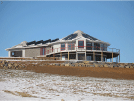 Image of a beautiful two story home exterior with solar panels and fiberglass deck out in the snow