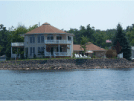 Image of a beautiful two story home exterior with double fiberglass deck by the lake