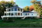 Image of a beautiful two story white home exterior with rap around deck with connecting wing