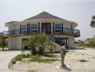 Image of a beautiful two story white home exterior with second floor deck on the beach