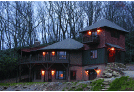 Image of a beautiful twp story with a tower home exterior in the woods
