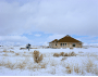 Image of a beautiful one story circular home exterior with a wing in the snow