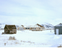 Image of a beautiful one story home exterior with a shack and gray gilding out in the snow
