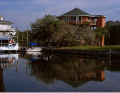 Image of a beautiful one story home exterior on SUSTAINABLE FIBERGLASS COMPOSITE PILINGS by the canal