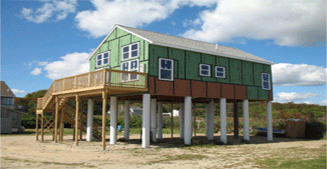Image of a green wood cabin way up on 15 feet of SUSTAINABLE pilings