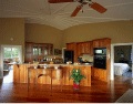 Image of an interior view of open plan kitchen in wood cabinets