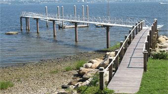 Image of a pier supported by SUSTAINABLE FIBERGLASS COMPOSITE PILINGS right of back yards