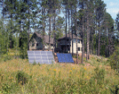 Image of homes using solar photovoltaics (panels on the left) for electricity and solar hot water for radiant floors and domestic hot water (panels on the right.)