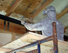 Image of an installer applying spray foam insulation to the underside of a Deltec roof.  Foam expands 200 times during installation, and cures into an inert plastic material that both insulates the roof and makes it air-tight